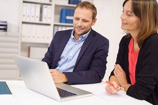 man and woman in business attire looking at a laptop