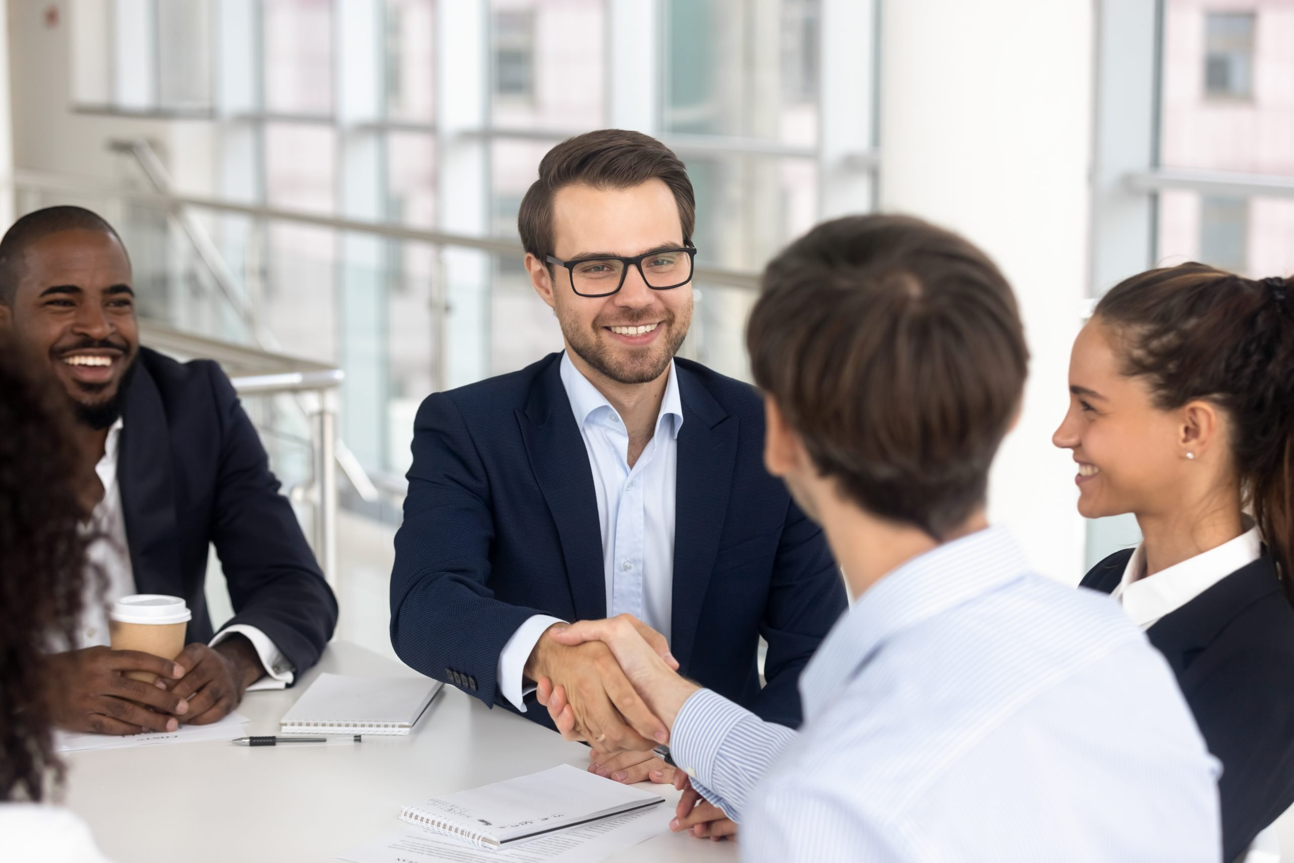 Happy smiling businessman handshake with business partner for successful agreement. African amercan and white men conclude profit deal with investor relationship good first impression, deal, respect