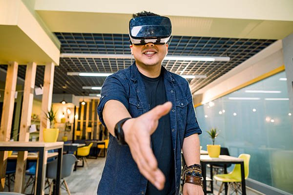 Young Chinese businessman working in office with virtual reality glasses on head. Man using VR headset for handshaking in augmented reality.