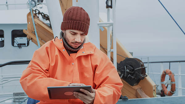 Dressed in Protective Coat Fisherman Using Tablet Computer with Navigation Maps while Traveling on Ship.