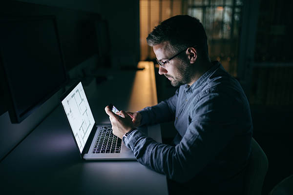 Young Caucasian businessman with eyeglasses using smart phone for writing or reading message while sitting in the office late at night. In front of him laptop. Side view.