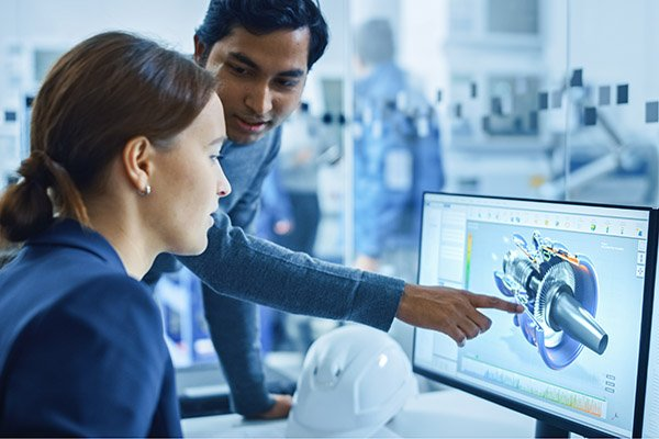 Modern Factory Office: Portrait of Male Project Supervisor Talking with a Female Industrial Engineer, They Point at Computer Display Showing CAD Software with 3D Engine Concept. Team Problem Solving